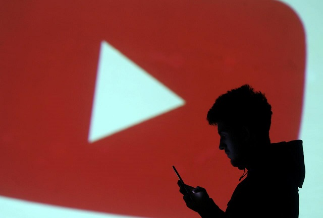 Silhouette of mobile user is seen next to a screen projection of Youtube logo in this picture illustration taken March 28, 2018.  PHOTO: REUTERS