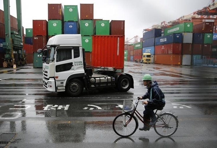 A worker rides a bicycle in a container area at a port. PHOTO: REUTERS