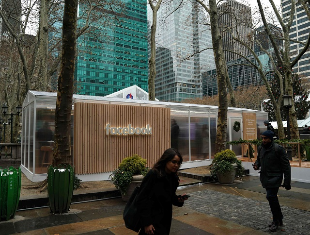 people walk by as the social network facebook opens a pop up kiosk for one day on december 13 2018 in bryant park in new york photo afp