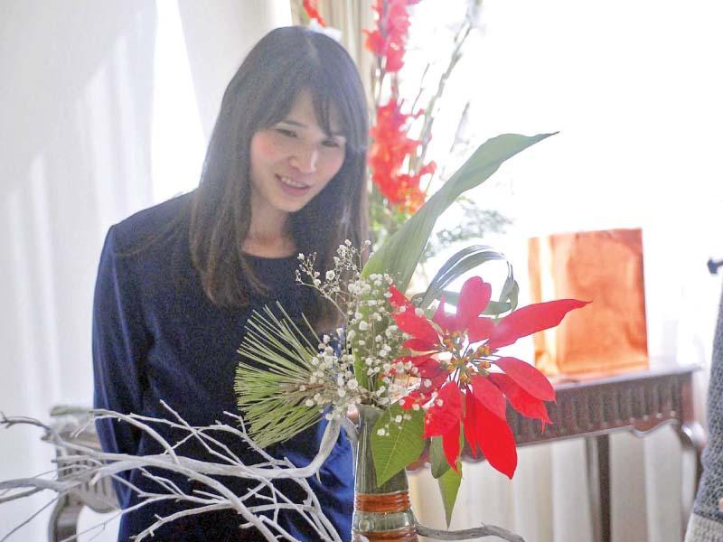 Wife of the Japanese Ambassador Madam Rieko Kurai explains floral arrangement during an Ikebana exhibition held at her home on Tuesday. PHOTO: DNA