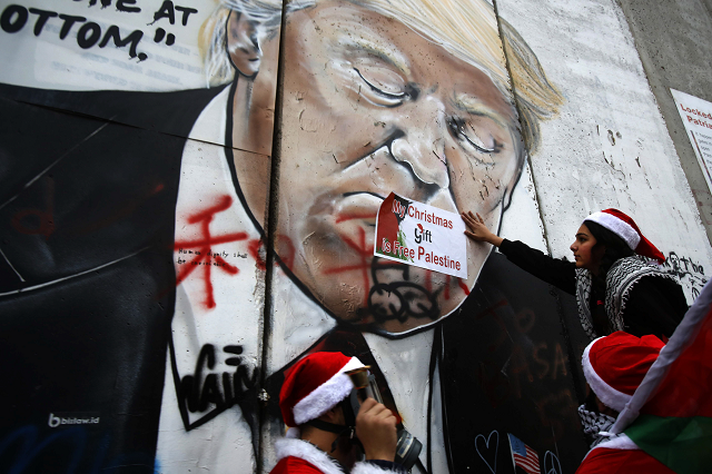 Palestinians dressed as Santa Claus, hang signs on a mural painting of US President Donald Trump on Israel's controversial separation barrier in the West Bank city of Bethlehem, on December 23, 2018. PHOTO: AFP