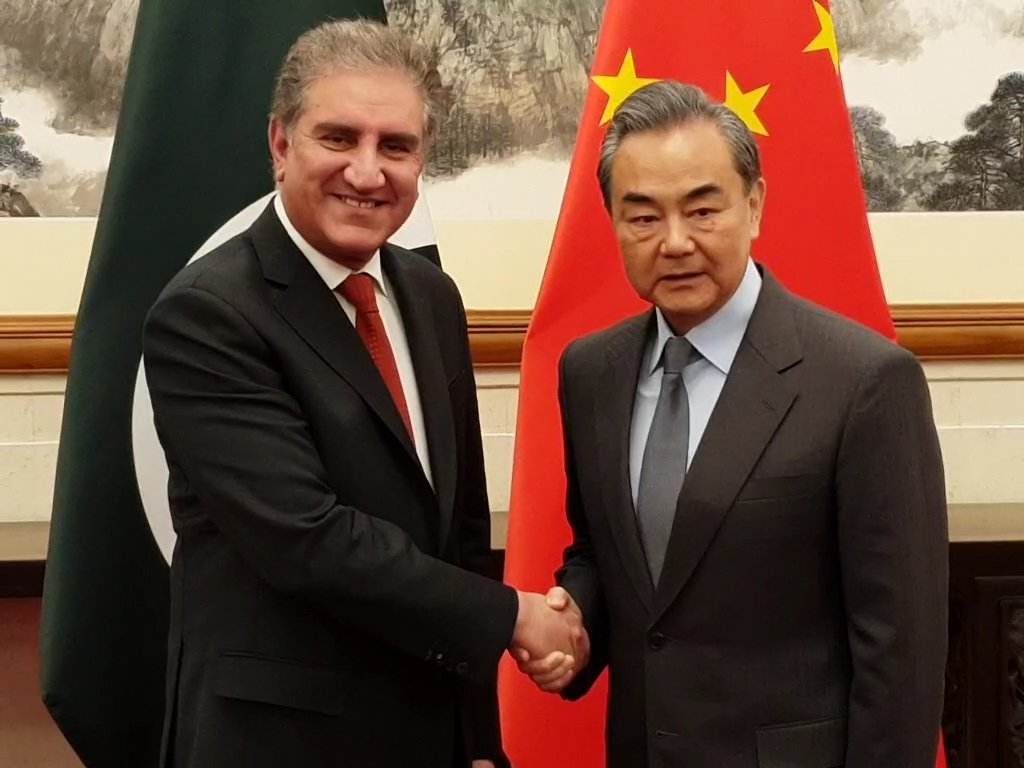 Foreign Minister Shah Mehmood Qureshi with his Chinese counterpart Wang Yi in Beijing. PHOTO: PTI