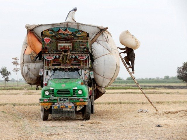 Workers load straw onto a decorated truck outside Faisalabad, Pakistan. PHOTO: REUTERS
