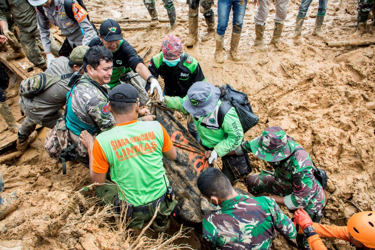 Rescue workers carry a body bag containing remains of victims following a landslide at Cisolok district in Sukabumi, West Java province, Indonesia. PHOTO: REUTERS