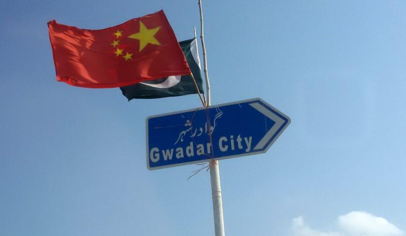chinese and pakistani flags fly on a sign board along a road towards gwadar photo file