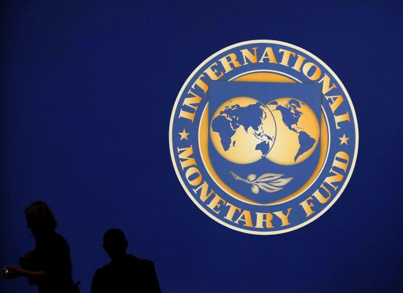 Visitors are silhouetted against the logo of the International Monetary Fund at the main venue for the IMF and World Bank annual meeting in Tokyo. PHOTO: REUTERS