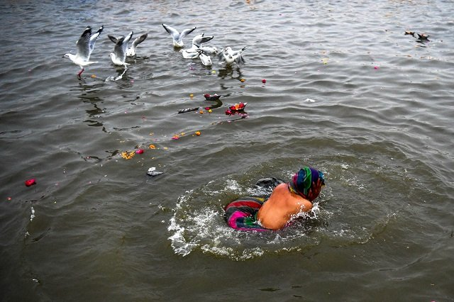 An Indian devotee takes a dip on the Triveni Sangam banks, the confluence of the Ganges, Yamuna and mythical Saraswati rivers, at the Kumbh Mela festival in Allahabad. PHOTO: AFP