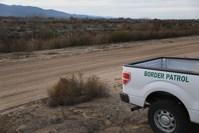 A US Border patrol vehicle is seen parked along the Rio Grande river ( just beyond the dirt road) that marks the border between Mexico and the United States. PHOTO:AFP