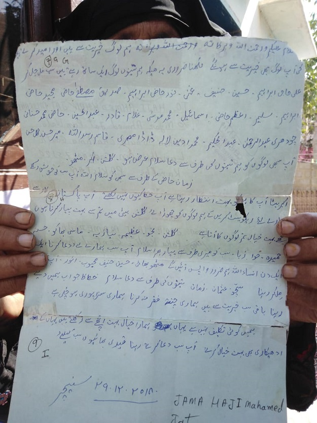 Woman holding letter sent by her brother (fisherman imprisoned in India). PHOTO: Express