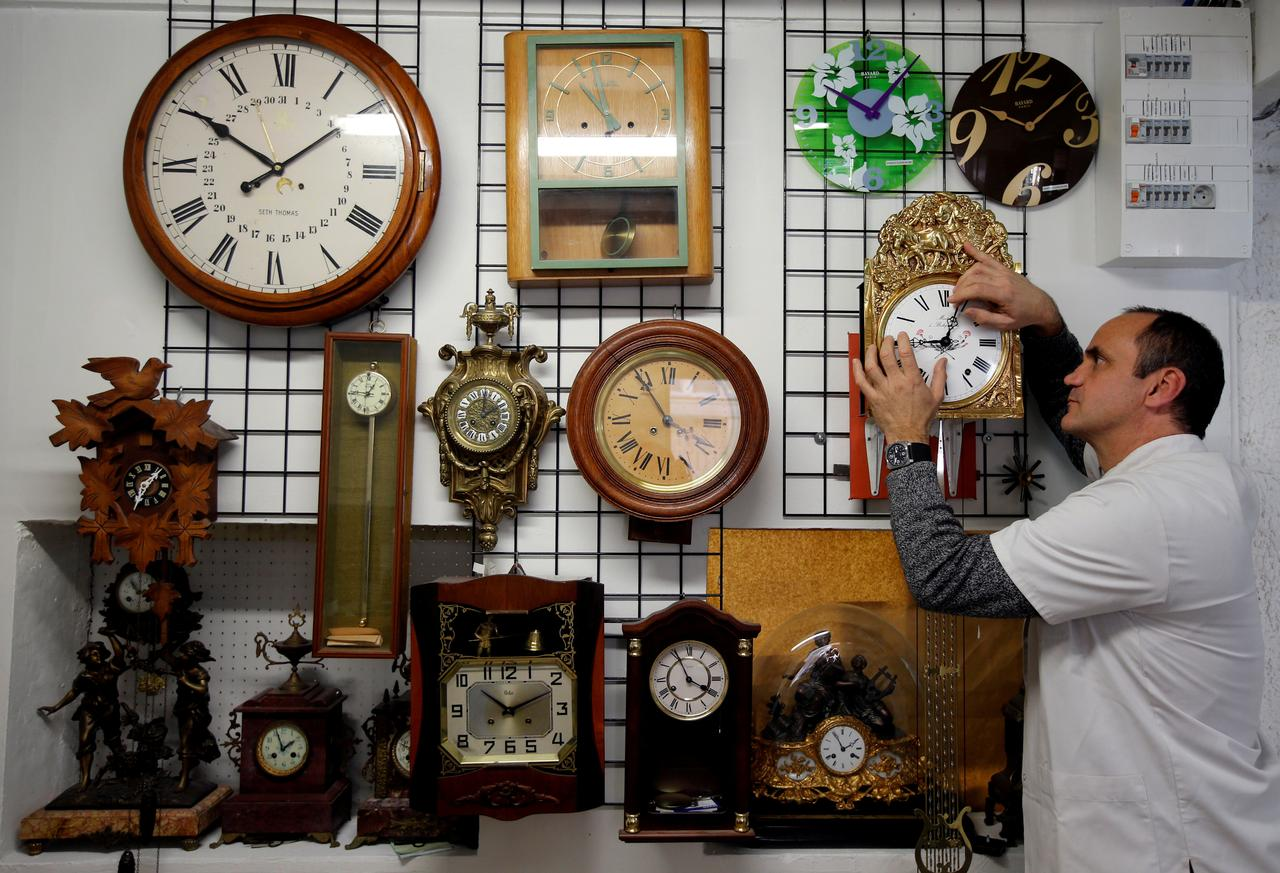 Serge Kertchef, a watchmaker, adjusts the hands on a wall clock in his workshop in Marseille, France PHOTO: REUTERS