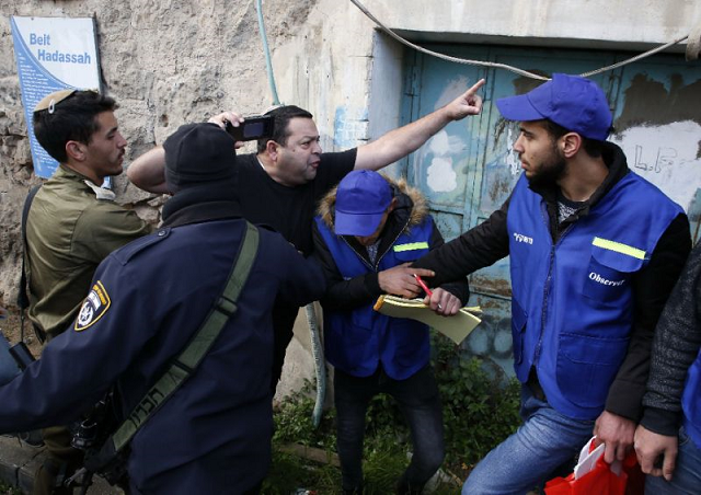 members of the israeli security forces intervene as a jewish settler c shouts at members of the palestinian youth against settlements yas activists r in the occupied west bank town of hebron photo afp