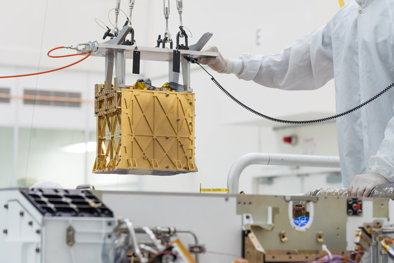 this handout photo obtained april 21 2021 and released by nasa jpl shows technicians in the clean room carefully lowering the mars oxygen in situ resource utilization experiment moxie instrument into the belly of the perseverance rover photo afp