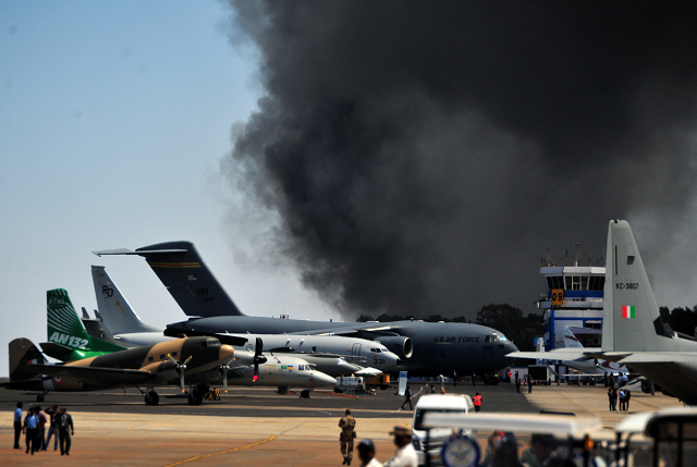 Smoke billows past a row of parked planes after a fire broke out in a parking lot during the Aero India show at the Yelahanka Air Force Station in Bengaluru, India, February 23, 2019. PHOTO: REUTERS