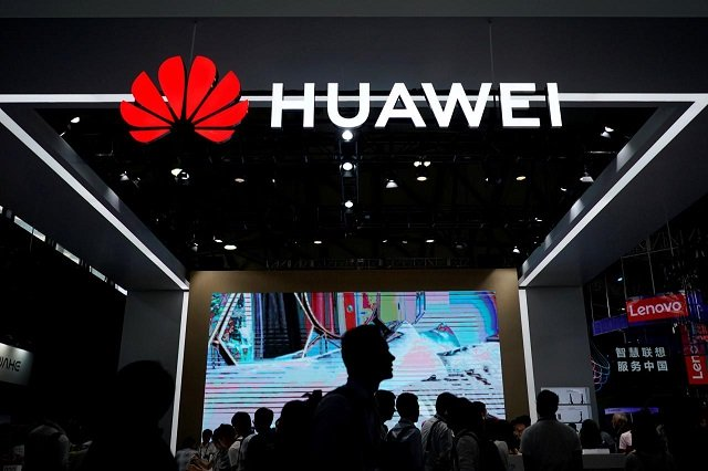 people walk past a huawei sign at ces consumer electronics show asia 2018 in shanghai china june 14 2018 photo reuters