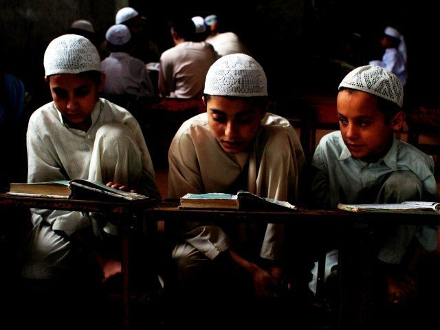 children reading at an islamic seminary in pakistan photo express file