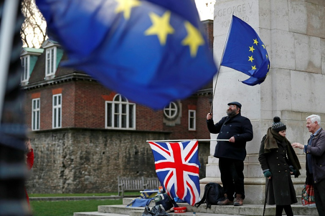 an anti brexit activist waves an eu flag and a union jack flag as he demonstrates opposite the houses of parliament in central london on january 9 2019 photo afp
