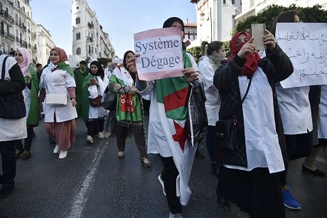 a woman holds a placard reading quot system get off quot as algerian teachers protest in central algiers on march 13 2019 against president abdelaziz bouteflika 039 s bid to prolong his two decade rule photo afp