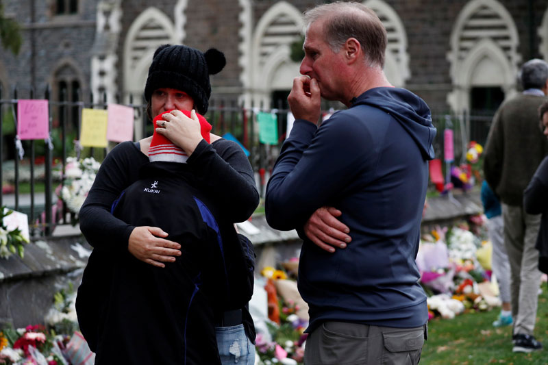 people react at a flower tribute area at botanical gardens in christchurch new zealand photo reuters