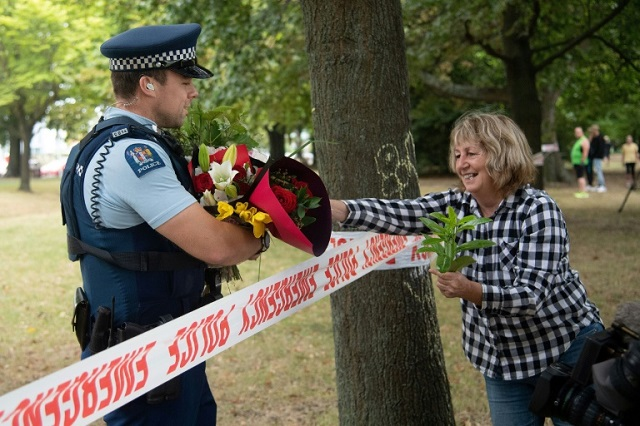 a woman hands flowers to a police officer to the dean avenue mosque in christchurch photo afp