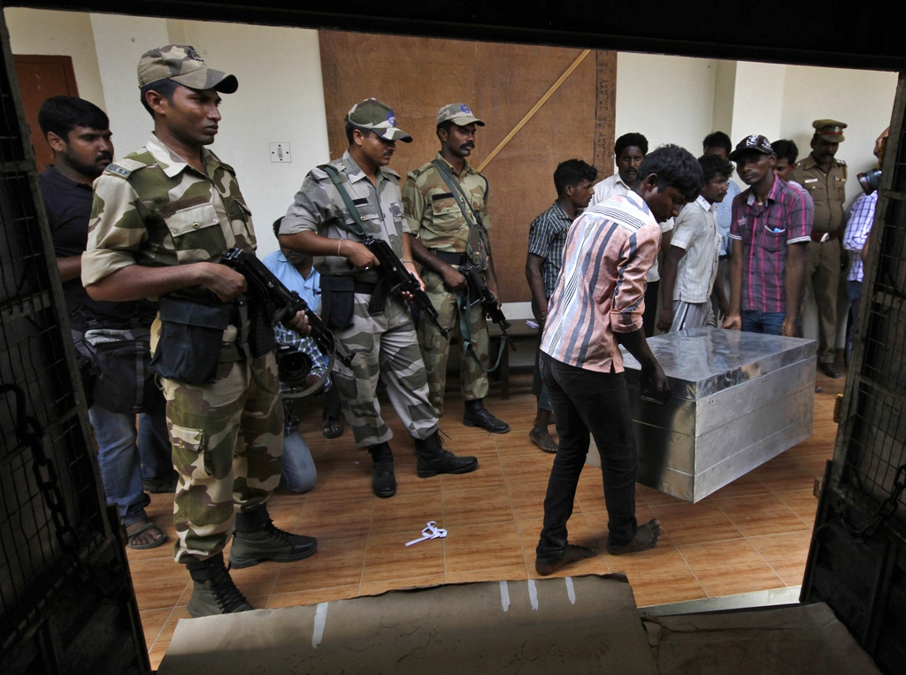 workers carry electronic voting machines evm in a trunk as indian security personnel stand guard at an election material distribution centre ahead of the sixth phase of the general election in the southern indian city of chennai photo reuters file