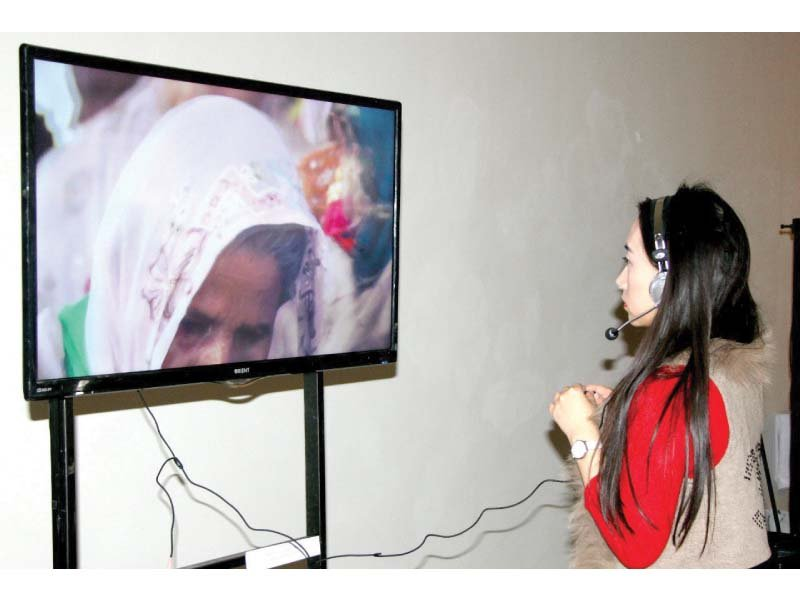 visitor at the ahang travelling exhibition admiring a video installation at the show photo express