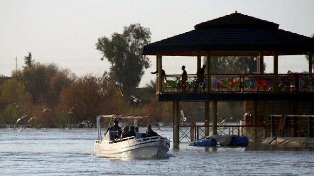 a boat passes the site of a popular mosul picnic area near where the ferry sank on thursday photo afp