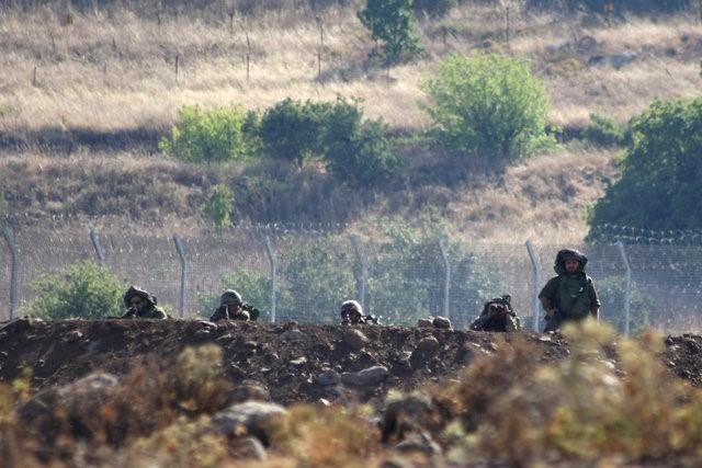 israeli soldiers take positions near the border between syria and the israeli occupied golan heights as seen from the syrian village of beer ajam photo reuters