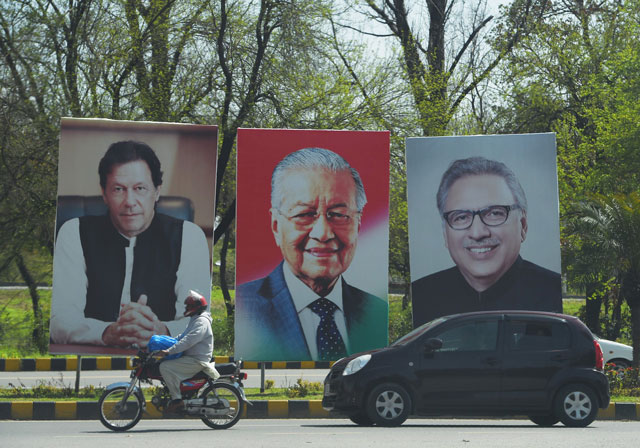 portraits of prime minister imran khan l president arif alvi r along with malaysia 039 s prime minister mahathir mohamad c on the constitution avenue in islamabad on march 21 2019 photo afp
