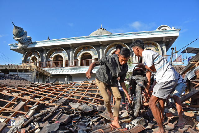 people in western lombok indonesia pulling a motorcycle from a damaged home near a mosque photo reuters