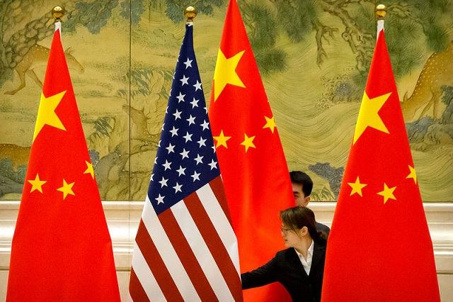 chinese staffers adjust us and chinese flags before the opening session of trade negotiations between us and chinese trade representatives at the diaoyutai state guesthouse in beijing thursday february 14 2019 photo reuters