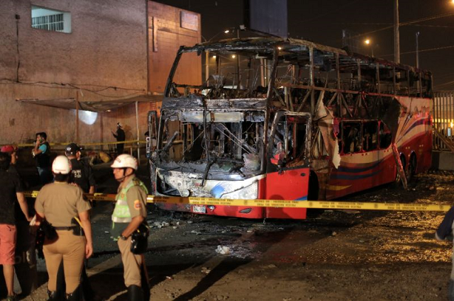 police stand around the charred remains of a bus that caught fire in lima killing 20 people photo afp