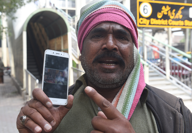 muhammad riaz father of 16 year old uzma a maid who was found dumped in a city canal shows her picture on a smartphone photo afp