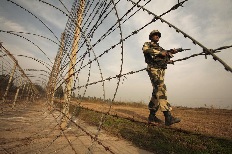 an indian border security force bsf soldier patrols near the fenced border with pakistan photo reuters