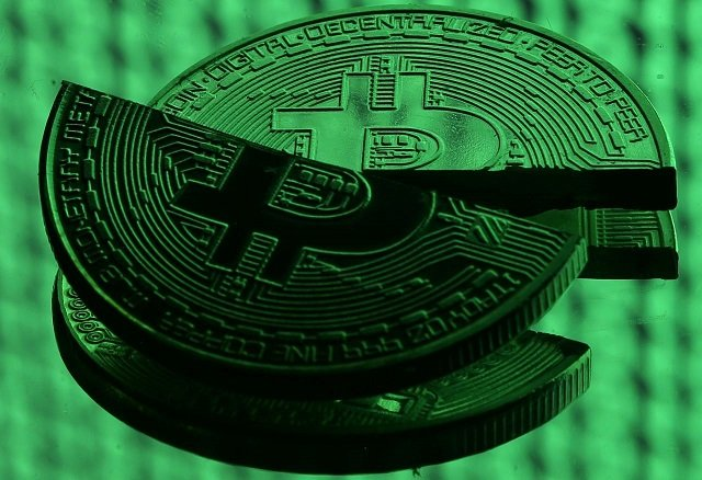 broken representations of the bitcoin virtual currency placed on a monitor that displays binary digits are seen in this illustration picture december 8 2017 photo reuters