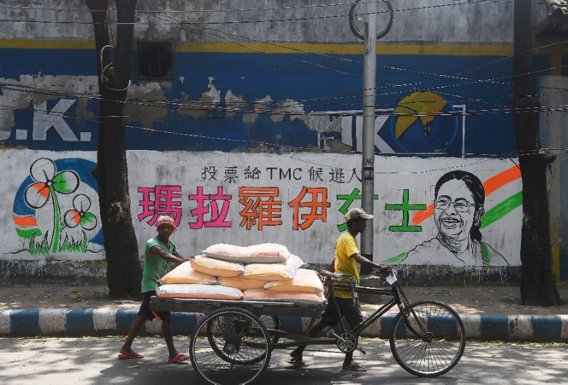 delivery men walk past a mural bearing chinese characters in support of a trinamool congress candidate in kolkata photo afp