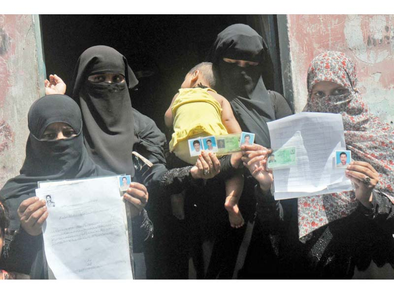 family members of pakistani fishermen who are imprisoned in indian jails hold up pictures of their loved ones seeking the government s help in securing their safe return photo ppi