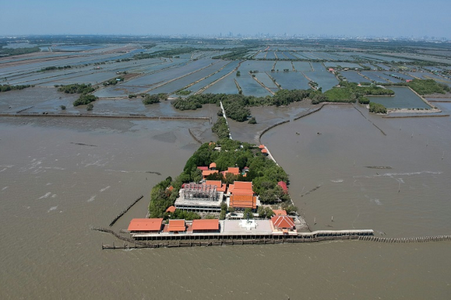a dangerous combination of climate change industrial farming and rapid urbanisation are endangering the gulf of thailand 039 s coasts stripping away precious mangrove trees and leaving some buildings like the temple at samut chin surrounded by sea water photo afp