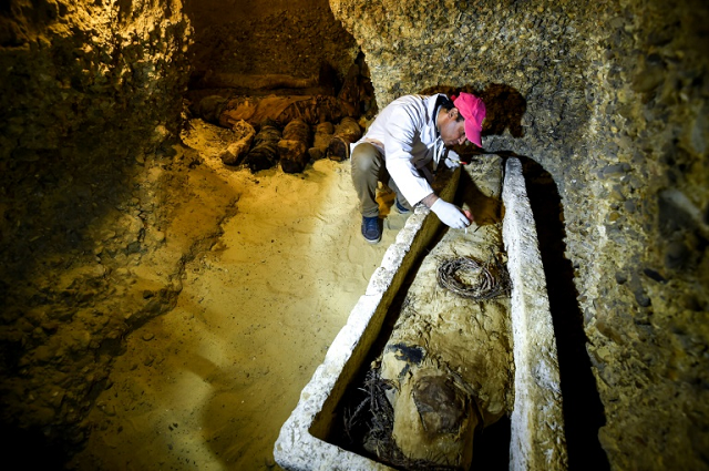 an archaeologist brushes a newly discovered mummy laid inside a sarcophagus part of a collection found in burial chambers dating to the ptolemaic era 323 30 bc in february 2019 photo afp