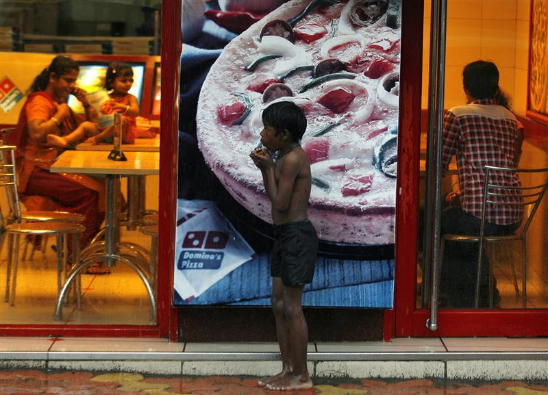 a homeless boy holds biscuits that he received as alms as he takes shelter from rain in front of a fast food shop in mumbai photo reuters