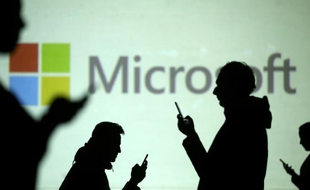silhouettes of mobile users are seen next to a screen projection of microsoft logo in this picture illustration taken march 28 2018 photo reuters