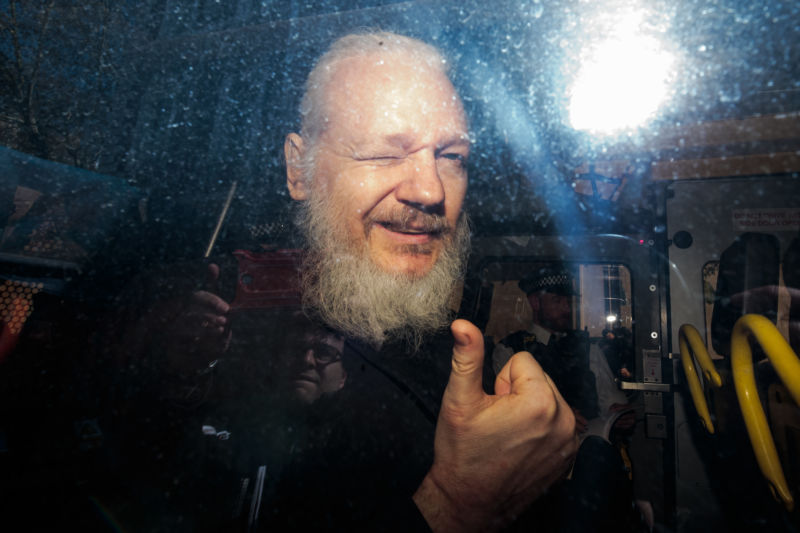 julian assange gestures to the media from a police vehicle on his arrival at westminster magistrates court on april 11 2019 in london england photo reuters