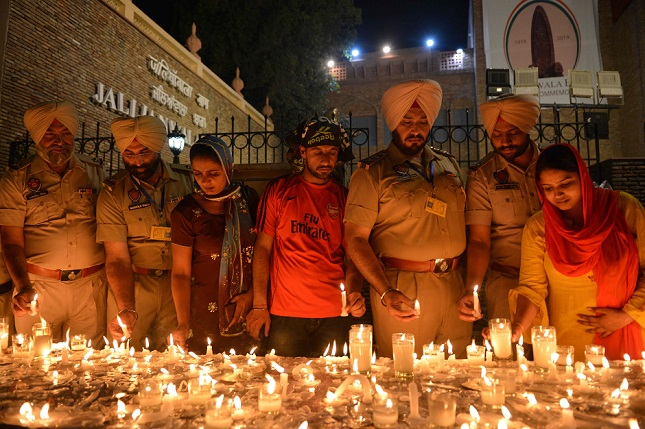 indian punjab police personnel light candles along with local residents as they pay tribute to those killed on the eve of the 100th anniversary of the jallianwala bagh massacre in amritsar on april 12 2019 photo afp