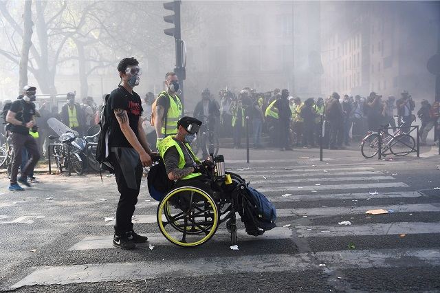 """A protester in wheelchair sits amid tear gas during clashes with police on April 20, 2019 in Paris, as thousands of """"Yellow Vest"""" (Gilets Jaunes) protesters took to the streets a 23rd week of anti-government marches. PHOTO: AFP"""