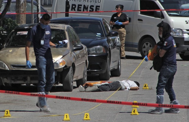 Forensic experts and investigators of the prosecution office work at the crime scene next to a man's corpse in Ciudad Juarez, Mexico, on April 20, 2019. PHOTO: AFP