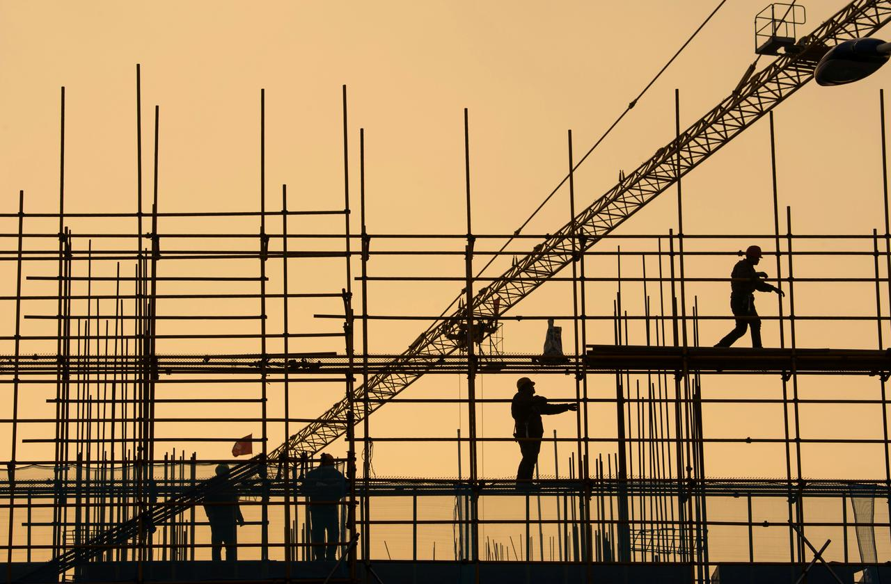 workers are seen on scaffolding at a construction site photo reuters
