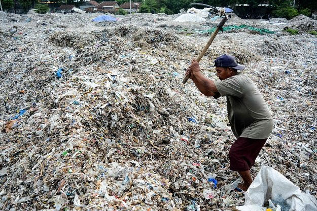 in this picture taken on december 11 2018 a man searches for plastic waste for resale at a dump in mojokerto east java province photo afp