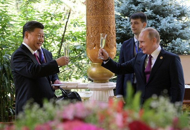 Russian President Vladimir Putin (R) toasts with Chinese President Xi Jinping while congratulating him on his birthday. PHOTO: REUTERS