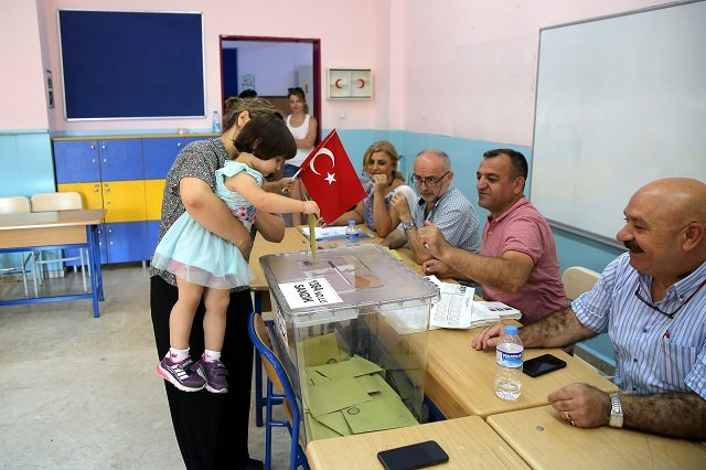 A woman holds a child who casts a ballot at a polling station during a mayoral election re-run in Istanbul, Turkey, June 23, 2019. PHOTO: REUTERS