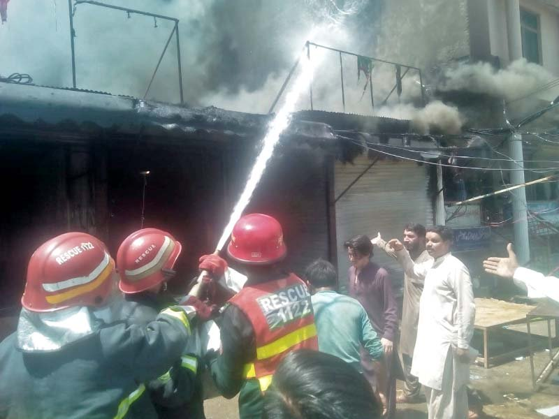 fire fighter trying to douse the fire which erupted in a market on chukri road photo express