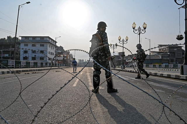 Indian paramilitary troopers stand guard behind a barbed fence wire as they block a road during a curfew in Srinagar. PHOTO: AFP